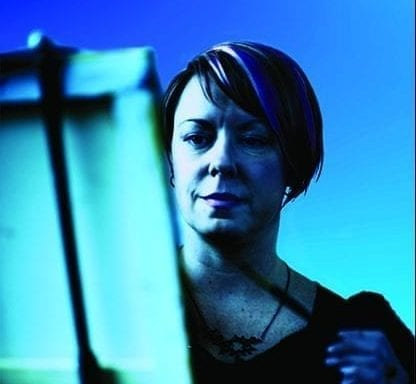 Headshot of female artist in front of easel